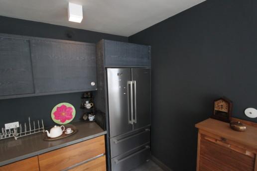zwarte keuken met kookeiland en doorlopend houtpatroon, meubelmaker amsterdam cabinetmaker custom furniture op maat gemaakt maatwerk meubels
