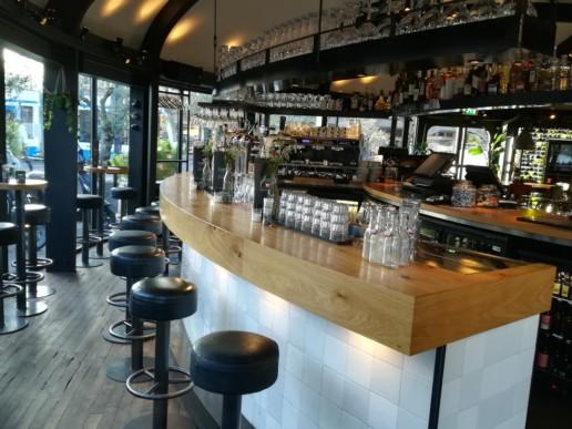 verhoogde bar witte tegels houten blad kassa wijnrek, meubelmaker amsterdam cabinetmaker custom furniture op maat gemaakt maatwerk meubels